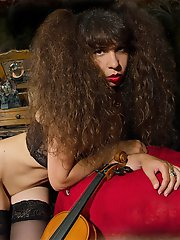 Kinky gothic brunette in black lingerie and black nylons stuffing her pussy with a dildo